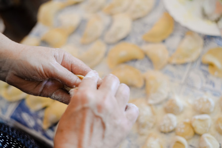 tortellini: Making dumplings, ravioli busy kitchen table background, close up top side view Stock Photo