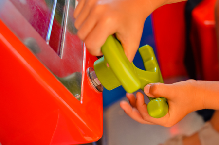 Close up on kid hands playing behind the wheel of a game console background. Electronic business entertainment activity. Playful education simulation technology Stock Photo