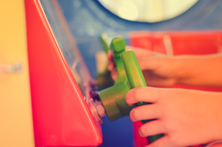 Close up on kid hands playing behind the wheel of a game console background. Electronic business entertainment technology simulation activity. Playful education