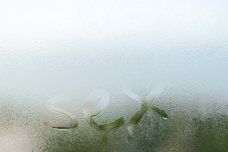 Closeup sign of on the foggy window glass with dripping drops condensated background, sensual steamy abstraction
