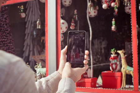 Close up on buyer hands using mobile phone choosing selecting purchase, taking picture of display window. Back side view photography of adult man tourist street shopping