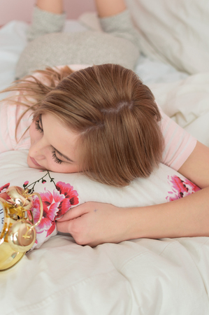 Closeup on woman with alarm clock in bedroom interior background. Relaxing dream time