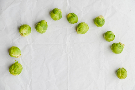 Brussels sprouts green vegetables on light table background. Flat lay close up top view copy space design. Health food lifestyle
