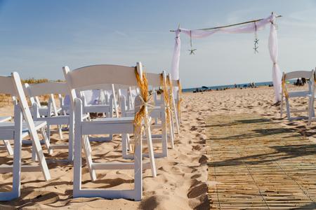 Dekoration von Seesternen, Blumen und Stroh, an einem Sandstrand für die Hochzeitszeremonie.