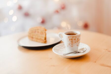 Italian coffee Cup and honey cake on the table near the white Christmas tree with golden bokeh