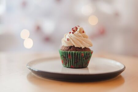 Green christmas cupcake with colorful sprinkles in pink cup on wooden background with garland lights bokeh
