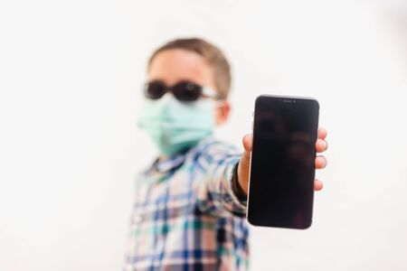 Young boy wearing disposable mask and sunglasses holding mobile phone over white background