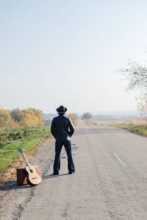 Lonely guitarist looking at empty country road in autumn.