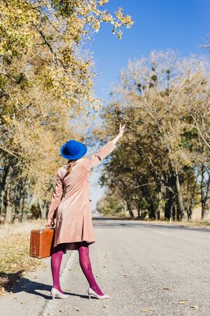 Young redhead lady woman in pink vintage coat and hat with suitcase in retro style walking away along a park road with golden yellow autumnal trees. Outdoor autumn garden relaxation, travel concept