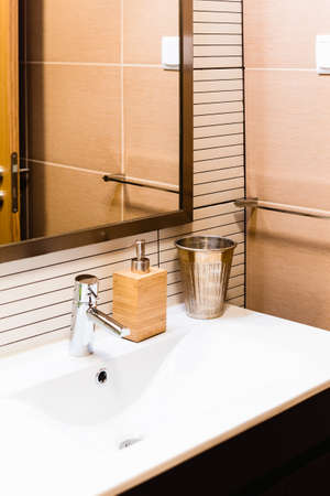 Ceramic Water tap sink with faucet with soap and shampoo dispensers in expensive loft bathroom