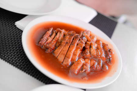 Roasted duck with Sauce, Chinese style on a white plate in buffet restaurant