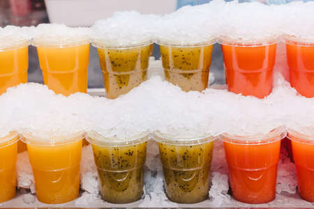 Fruit juice mix with ice arranged in plastic cups on a market stall with small fork inside, takeaway snack