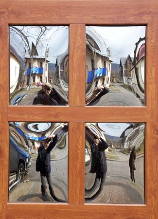 男はミラーの正面玄関のウィンドウ ガラスの家でき馬 写真素材