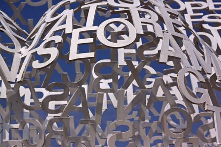 Composition with white letters on a blue sky. Detail of sculpture Nomad, 2010. Painted stainless steel by Jaume Plensa (Barcelona, ??Spain). Antibes, Cote dâ??Azur, France. June 30, 2016. The Blurred background