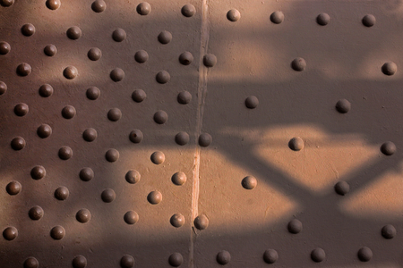 Close-up big convex rivets on metal surface background painted brown