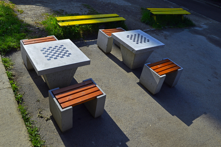 Stock Photo   Two Concrete Chess Tables, Four Chairs And Two Yellow Lavas