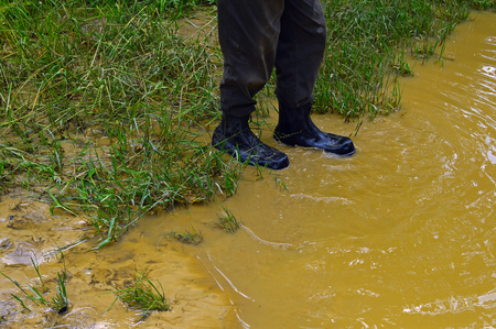 A man in rubber boots is in the puddle of muddy water