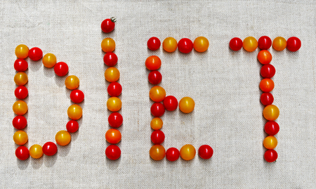 The word DIET is made up of small tomatoes of red and yellow color Stock Photo