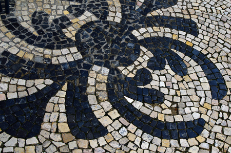 Stone mosaic of basalt and limestone on the street of Lisbon, Portugal.