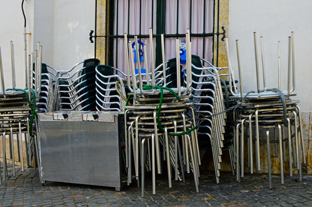 Folding chairs and tables of a street cafe in the morning