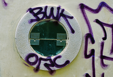 A small round window is painted with graffiti 写真素材