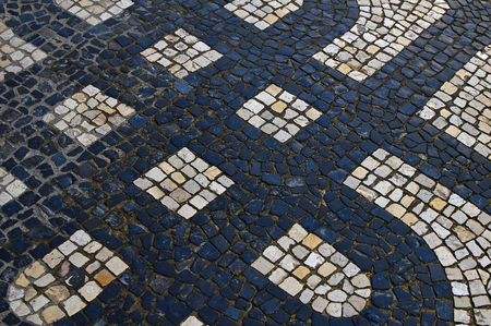 Traditional portuguese stone mosaic calcade with basalt and limestone in Lisbon, Portugal