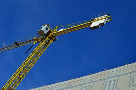 Yellow crane works in the city. Horizontal photo