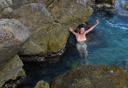 A young woman without a swimsuit in sea water among large stones