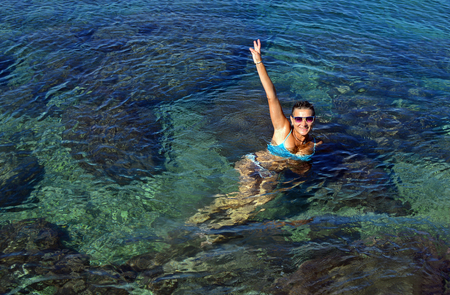 A young woman in swimsuit floats in seawater. Large space for writing