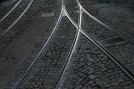 Tram rails and hatchs on an old cobbled road 写真素材