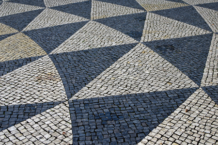 Traditional portuguese stone mosaic calcade with basalt and limestone on Municipal Square in Lisbon, Portugal