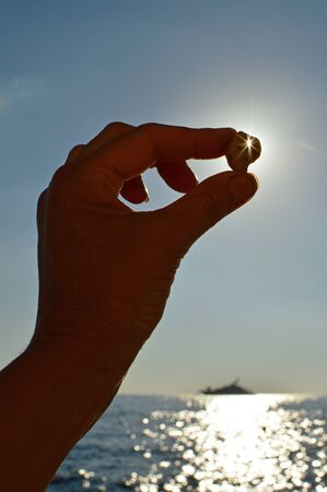 Girl holding a pebble with a hole on the background of the sky, sun, sea and yacht. Selective focus