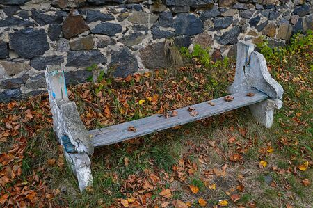 Old bench among yellow leaves near stone wall in park
