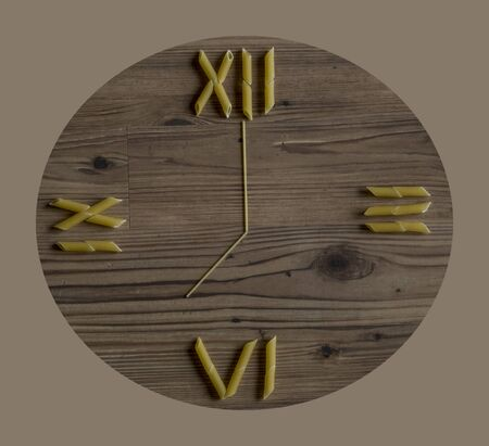 seven o'clock: Pasta laid out as clock flat on wood background Stock Photo