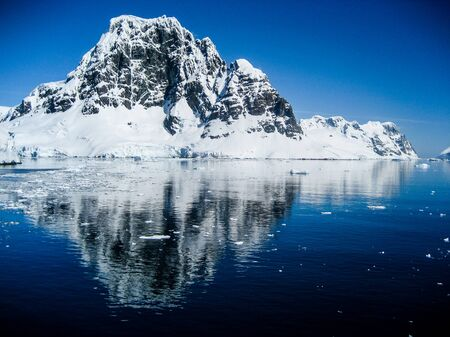 Snowy mountain reflected in Antarctic Ocean with clear blue skies