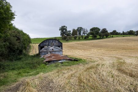 recently: Rusty old barn beside recently harvested field