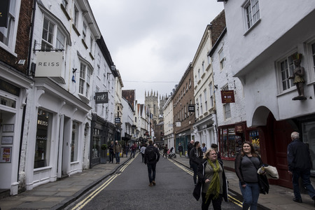 york minster: YORK, ENGLAND - 27 MAY 2016 - Unidentified shoppers stroll through a street in York with York Minster in the background