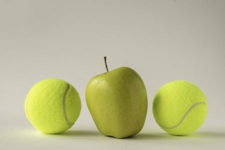 'odd one out': Odd one out - shiny yellow apple between two tennis balls against white background Stock Photo