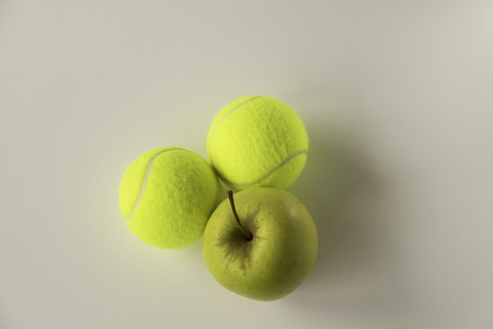 'odd one out': Two tennis balls with golden yellow apple on white background Stock Photo