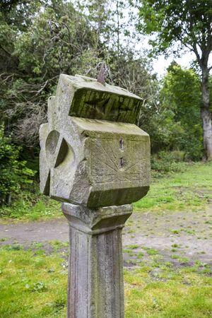 reloj de sol: Antiguo reloj solar de piedra cubierta de liquen en el bosque Foto de archivo