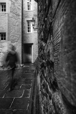 mile high city: Motion blur as a man walks through one of the many narrow closes (lane) off the Royal Mile in Edinburgh, Scotland Stock Photo
