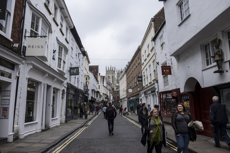 york minster: YORK, ENGLAND - 27 MAY 2016 - Unidentified shoppers stroll through a street on York with York Minster in the background