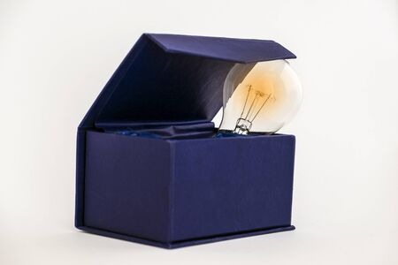 outside the box thinking: Bulb in blue box against white background with copy space signifying thinking outside the box concept