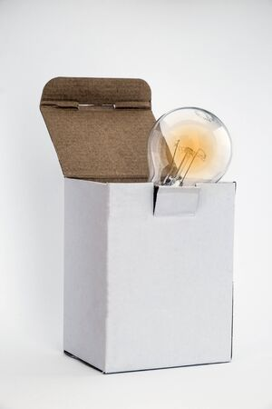thinking outside the box: Glowing bulb in white box signifying thinking outside the box concept with room for text on box and white background copy space Stock Photo