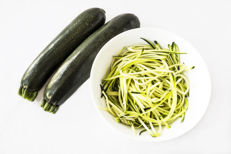 spiralized: Two zucchini or courgettes with some spiralized in a white bowl on white background