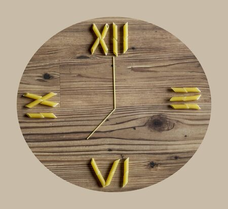 seven o'clock: Penne pasta and spaghetti laid out on wooden background as a clock Stock Photo