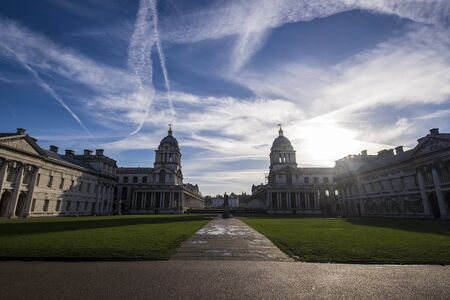 vapour: Panorama of Greenwich buildings, London against blue sky with vapour trails