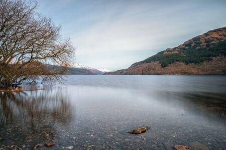 loch lomond: Long exposure of calm waters of Loch Lomond with snow covered mountains in the distance Stock Photo