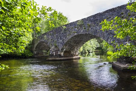 arcos de piedra: The arches of the stone hump back bridge over the River Balvag at Balquhidder, Scotland.