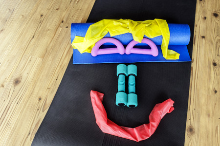 hand weights: Resistance bands and hand weights on yoga mats set out in a simley face pattern on wooden floor background